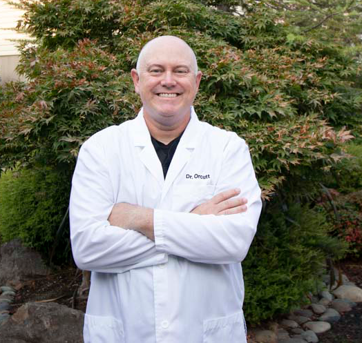 Dr. Brian Orcutt smiling, with his arms crossed standing outside in front of trees