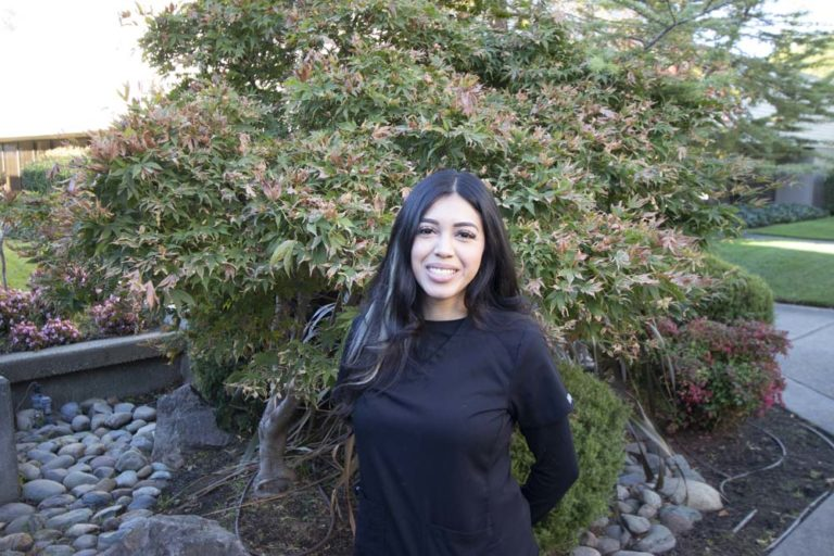 team member anaise standing in front of trees